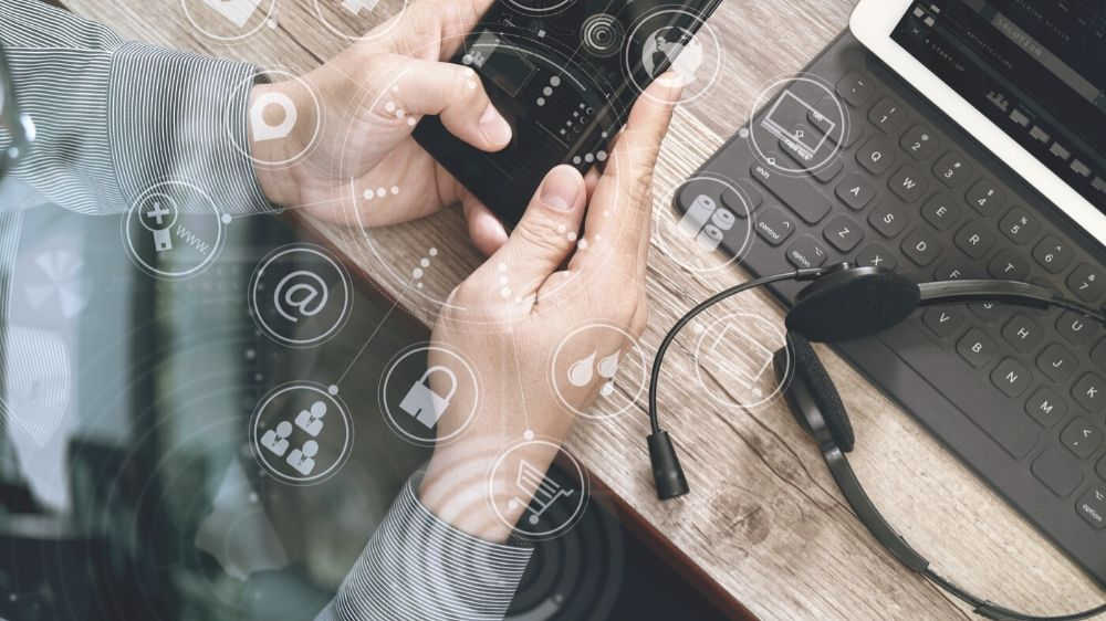 Close Up of Hands Using Smart Phone with Laptop and Headphones on Desk