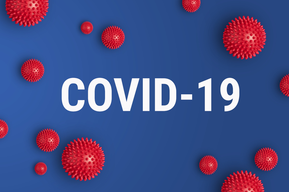The word COVID-19 over a blue background with red 3d models floating around it to represent the virus