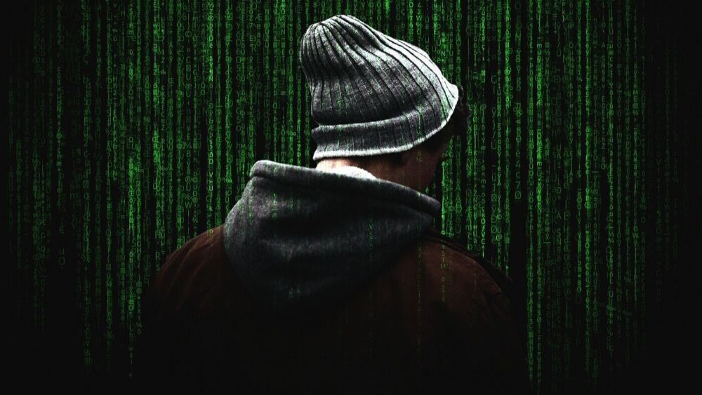 Man in Hoodie on Background of Green Computer Code