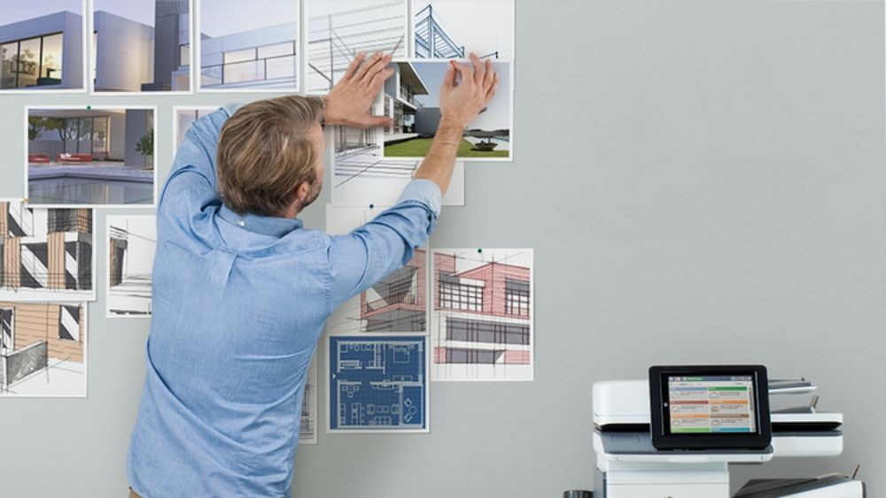 Man Pinning Printed Images to Office Wall