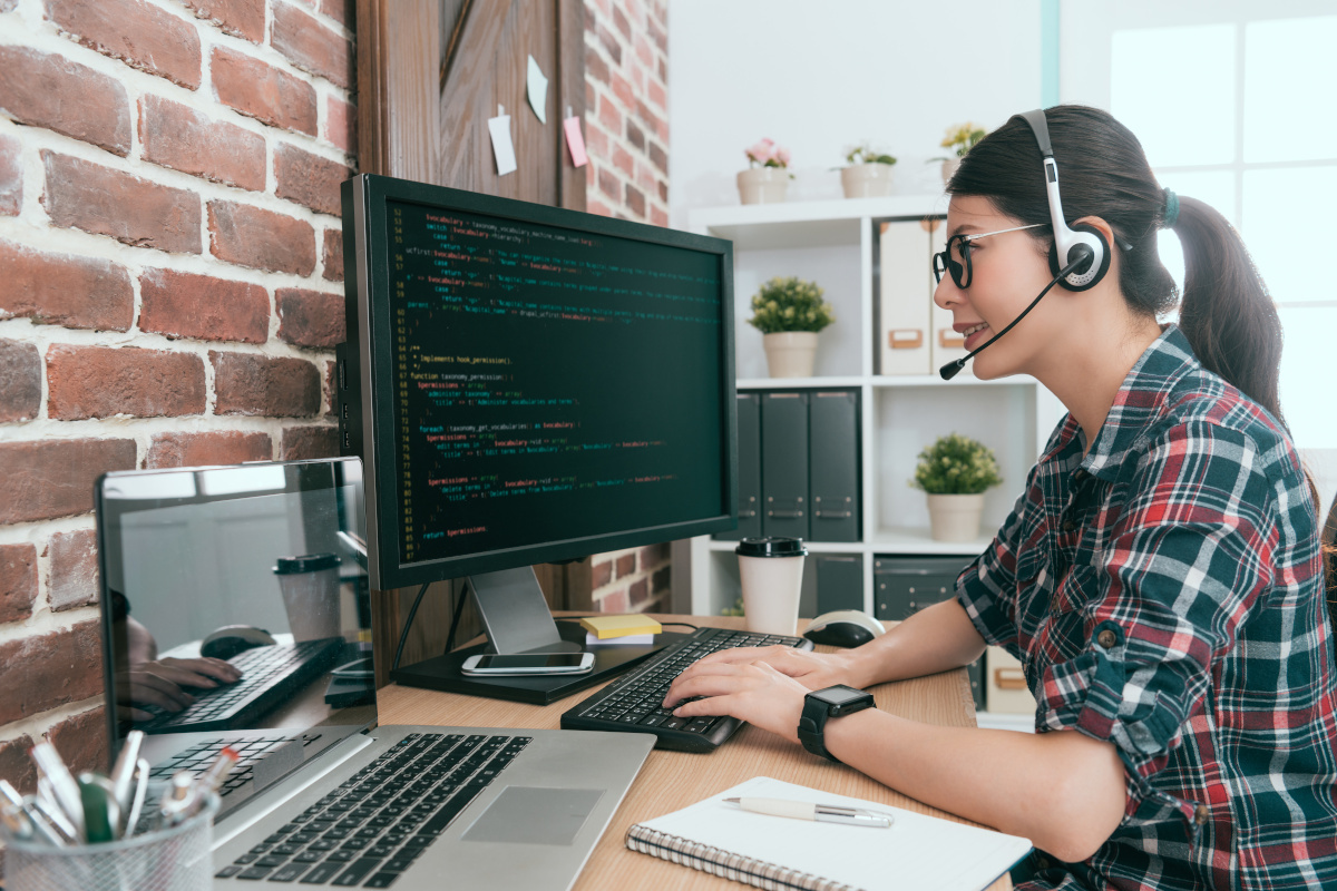 A man woman wearing a headset while working on code in her home office