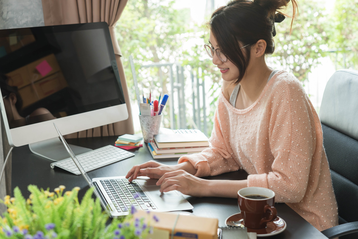 A woman in a sweeter working at on her laptop at her office desk at home